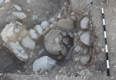 Figure 6. A bin built up against an Iron Age wall, lined with clay and a recycled grinding stone; the bin contains a large, reconstructable vessel.